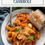 Overhead image of a plate of chicken parmesan casserole with noodles and text title box at top