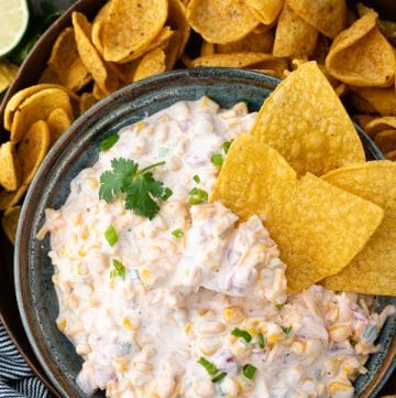 Bowl of creamy corn dip with tortilla chips on the side