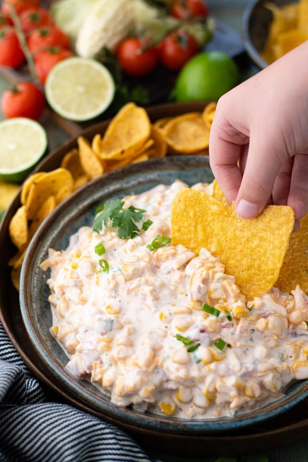 Dipping a tortilla chip in mexican corn dip