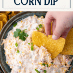 Hand dipping a chip in corn dip with text title box at top