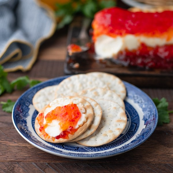 Cream cheese and pepper jelly crackers on a small blue and white plate