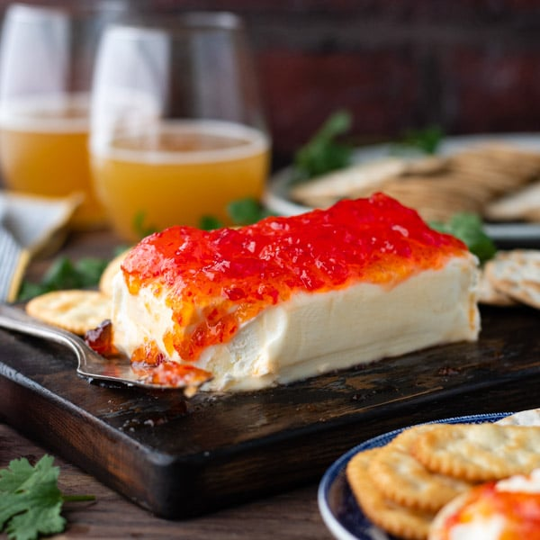 Square image of hot pepper jelly and cream cheese on a board with drinks in the background