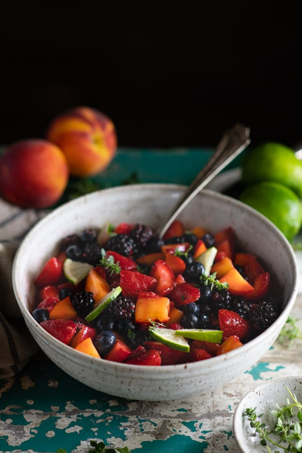 Side shot of a bowl of easy fruit salad with vanilla pudding on a vintage table
