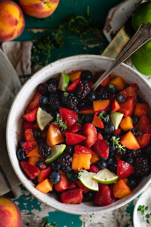 Close overhead image of a bowl of homemade fruit salad with vanilla pudding and fresh lime