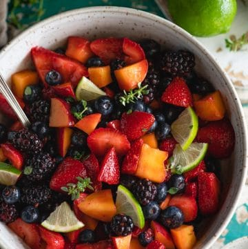 Close overhead image of a bowl of the best fruit salad recipe served in a white handmade bowl