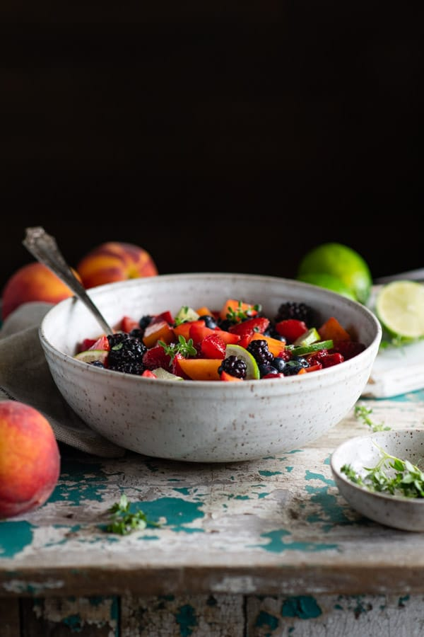Side shot of fresh fruit salad on a table in front of a dark background