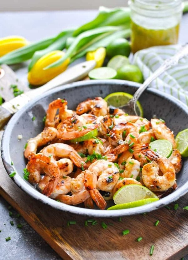 Marinated grilled shrimp in a dish with limes