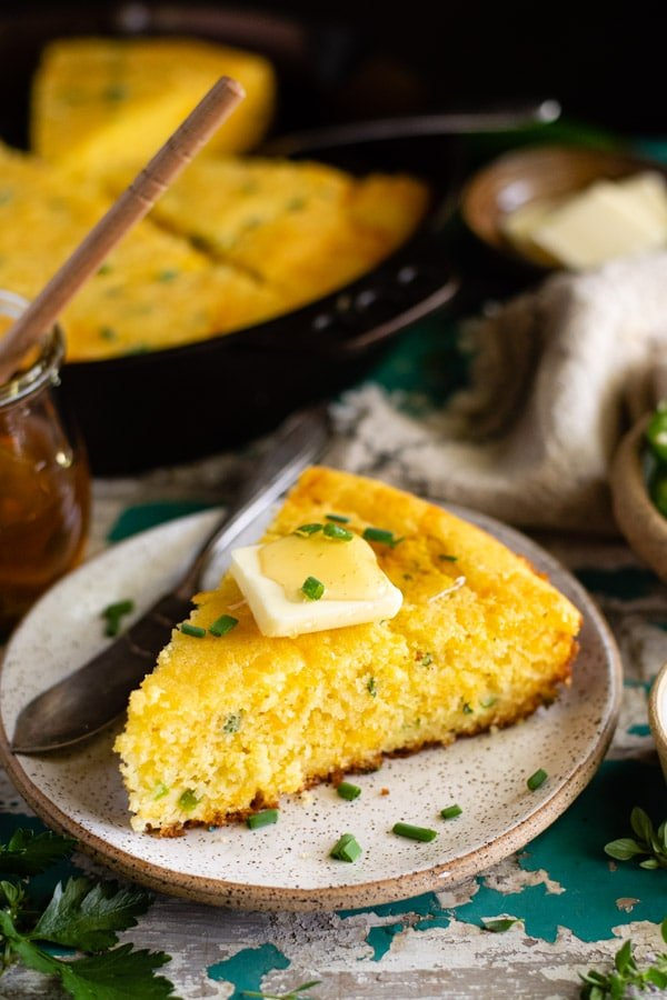 Slice of southern mexican cornbread with butter and honey on top