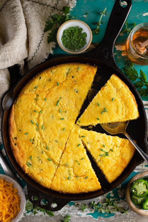 Sliced mexican cornbread in a cast iron skillet