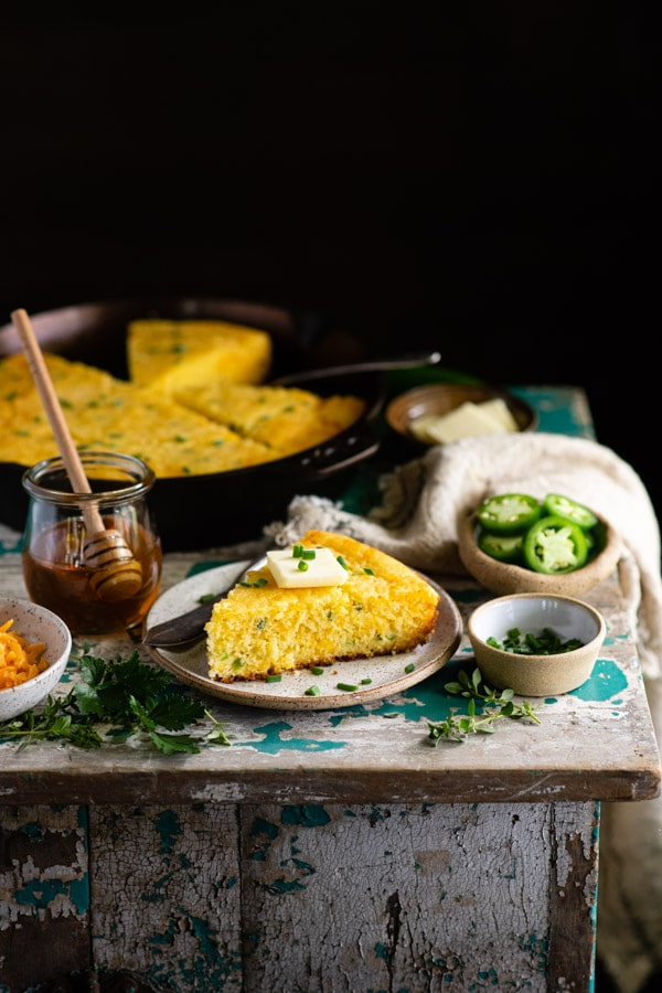 Table full of mexican style cornbread with toppings
