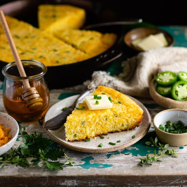 Square image of mexican cheesy cornbread on a table with honey and jalapenos nearby