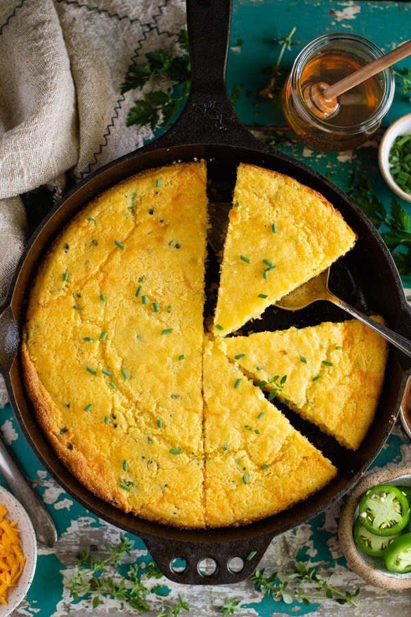 Overhead image of a cast iron skillet of mexican cornbread on a rustic farm table