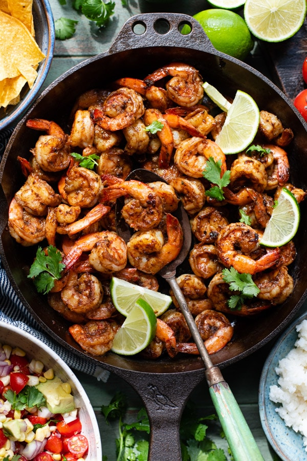 Overhead image of a pan of taco seasoned shrimp with fresh limes and cilantro