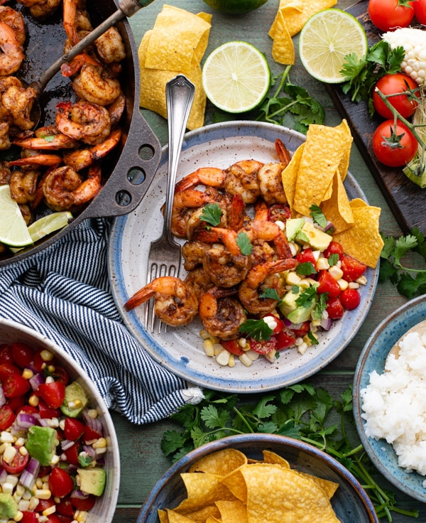 Overhead image shot of a green table full of Mexican shrimp with fresh tomato and corn salsa