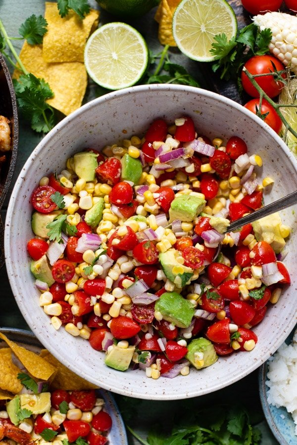 Bowl of fresh tomato salad with corn avocado and red onion