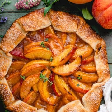 Overhead image of a spiced rustic peach galette on a green wooden table