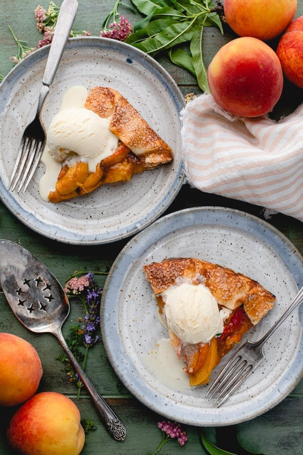Overhead shot of two slices of peach galette on plates with ice cream