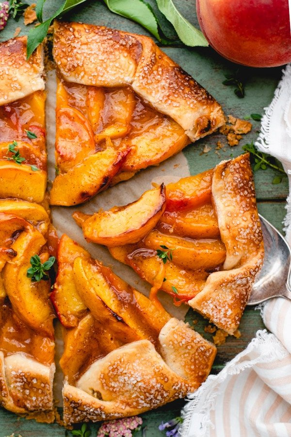 Close overhead image of a slice of peach galette with store bought crust on a server