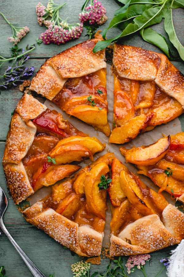 Overhead image of a sliced rustic peach galette on a green surface
