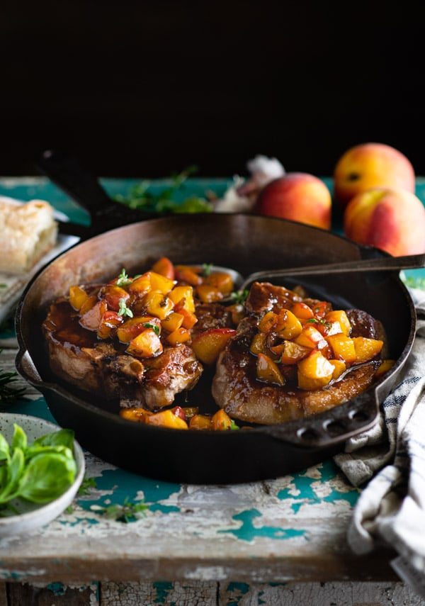Side shot of bone in thick cut pork chops in a cast iron skillet with fresh peaches