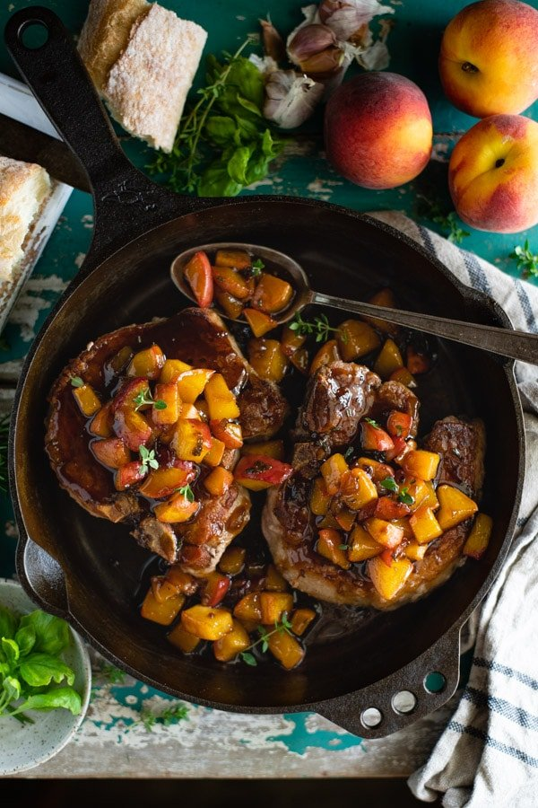 Overhead shot of a cast iron skillet with fried pork chops and peach sauce.