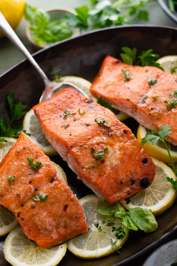 Close up side shot of roasted salmon fillets in a pan