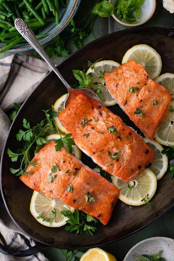 Glazed roasted salmon recipe served with lemon and fresh herb garnish