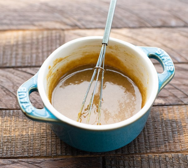 Brown sugar and Dijon mustard glaze in a small bowl with a whisk