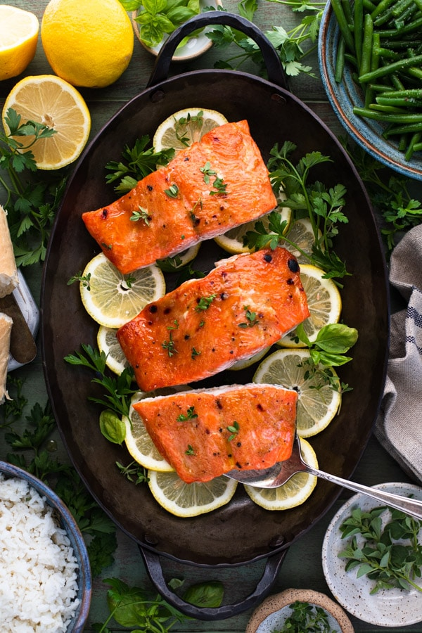 Overhead shot of oven roasted salmon on a serving platter with a side of bread