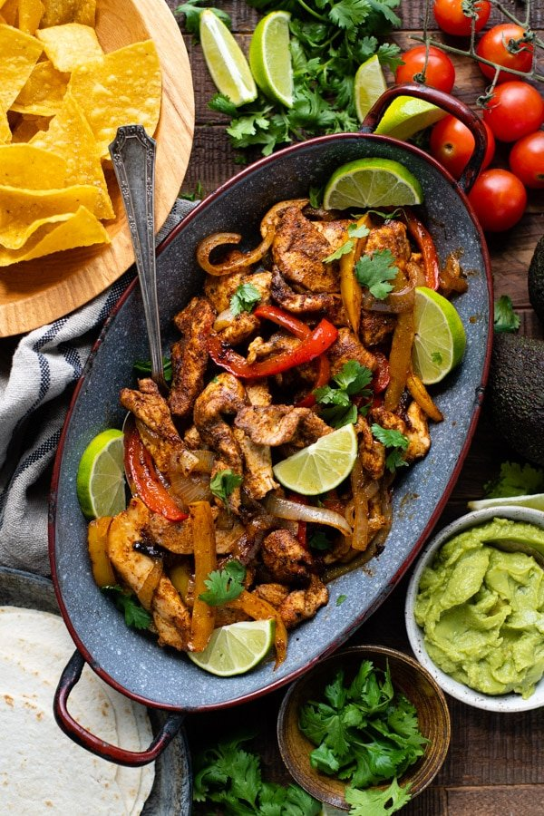 Sheet pan chicken fajita recipe served on a wooden table with plenty of toppings, tortillas and sides.