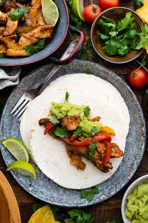 Overhead shot showing how to serve chicken fajitas on flour tortillas
