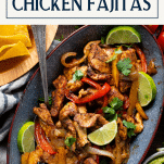 Overhead shot of a tray of restaurant style chicken fajitas with text title box at top