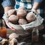 Front shot of hands serving a basket of homemade apple cider donut muffins