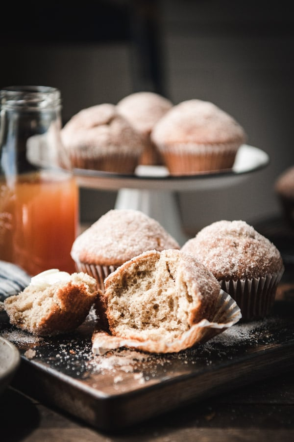 Side shot of cinnamon sugar donut muffins with a bite taken out