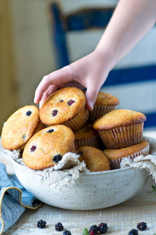 Child's hand picking up a blackberry muffin