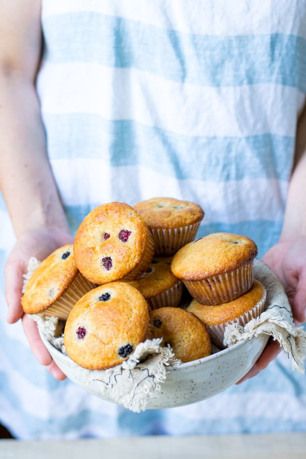 Hands holding a basket of blackberry muffins made from scratch