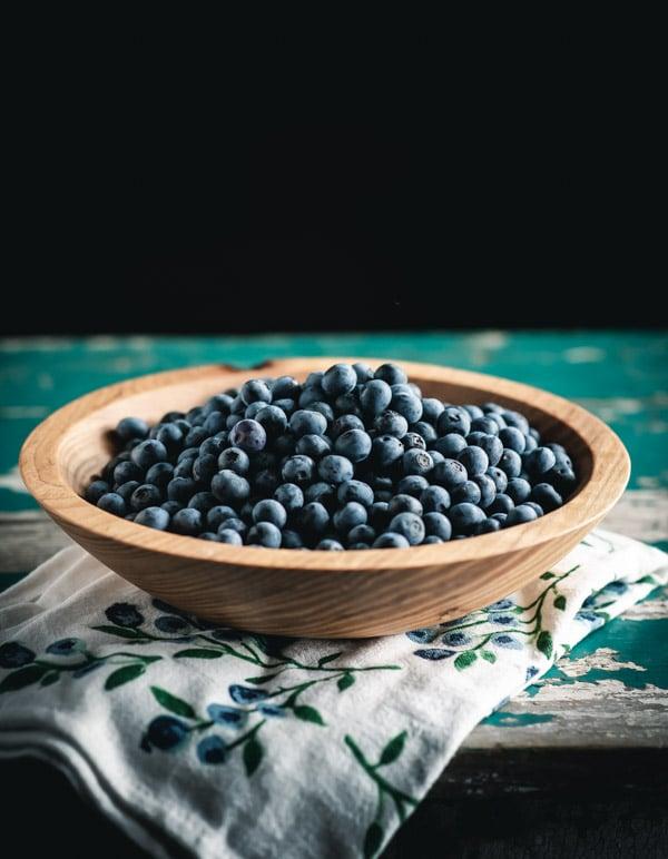 Wooden bowl full of fresh blueberries
