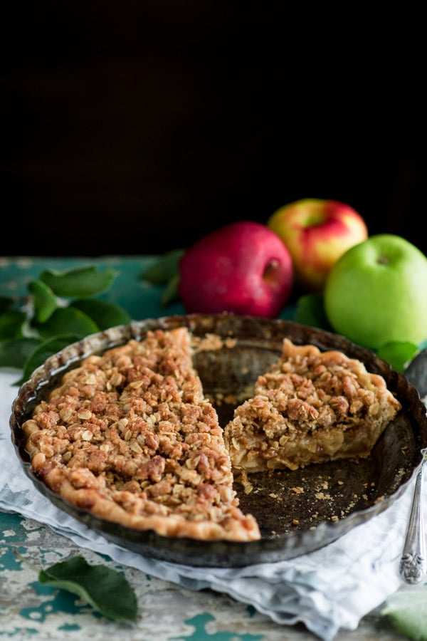 Apple crumble pie in a vintage pie plate on an old chest