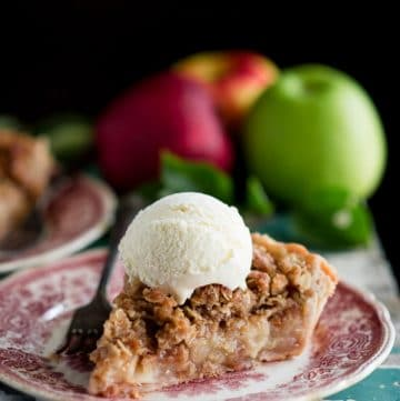 Side shot of a slice of apple pie with crumb topping on a plate