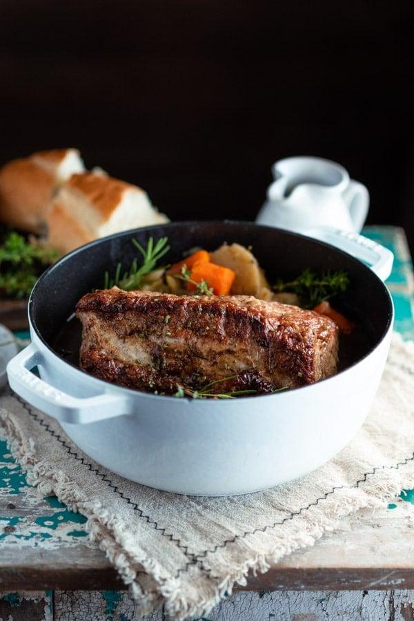 Side shot of pork loin roast in a white Dutch oven