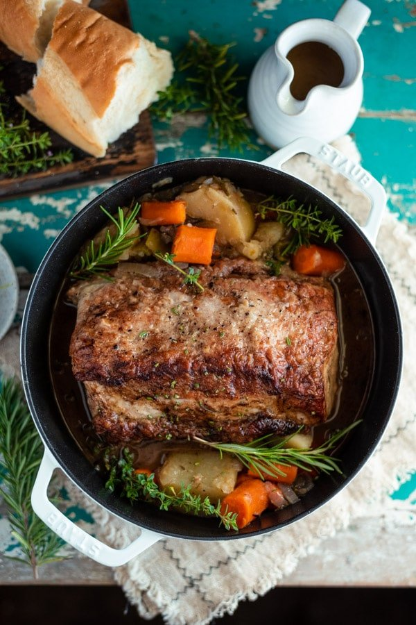 Overhead shot of Dutch oven pork roast on a table with bread