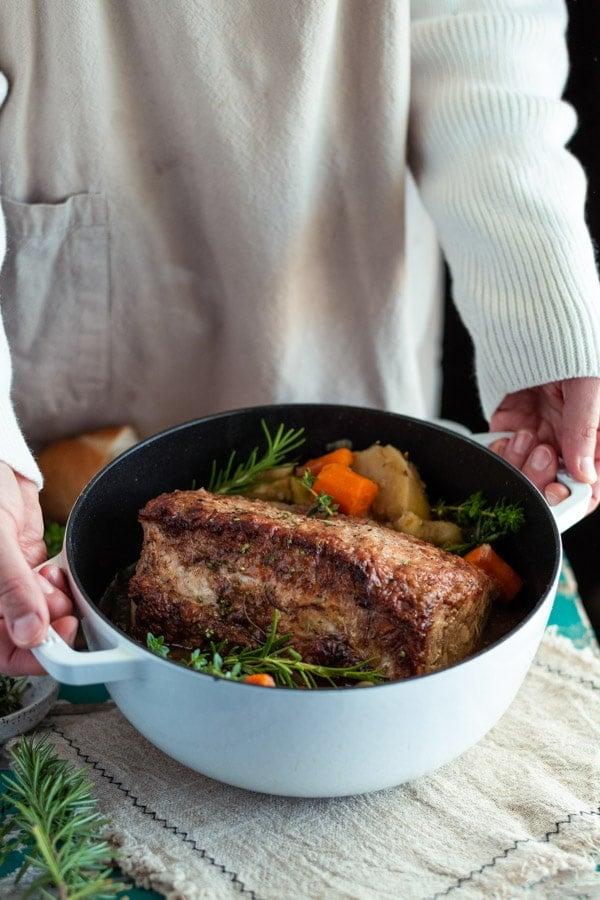 Hands holding a Dutch oven with a pork loin roast