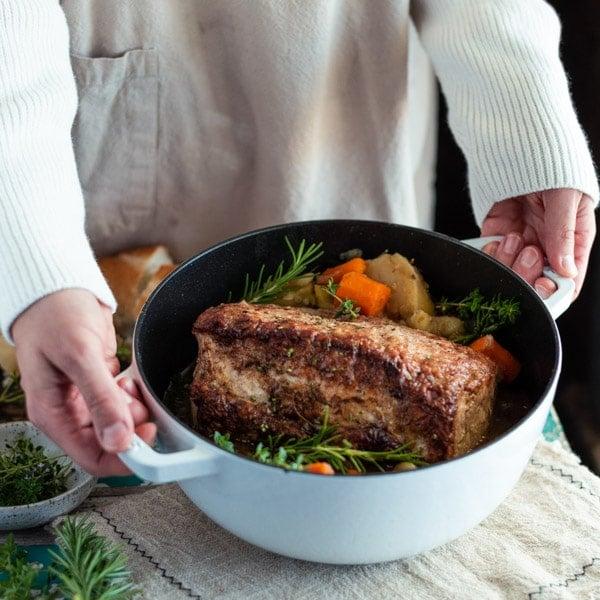 Square shot of hands serving pork loin roast recipe in a Dutch oven