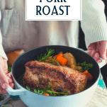 Hands holding a Dutch oven with roasted pork loin with text title overlay