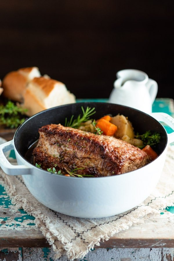 Side shot of a white Dutch oven with a simple pork roast recipe