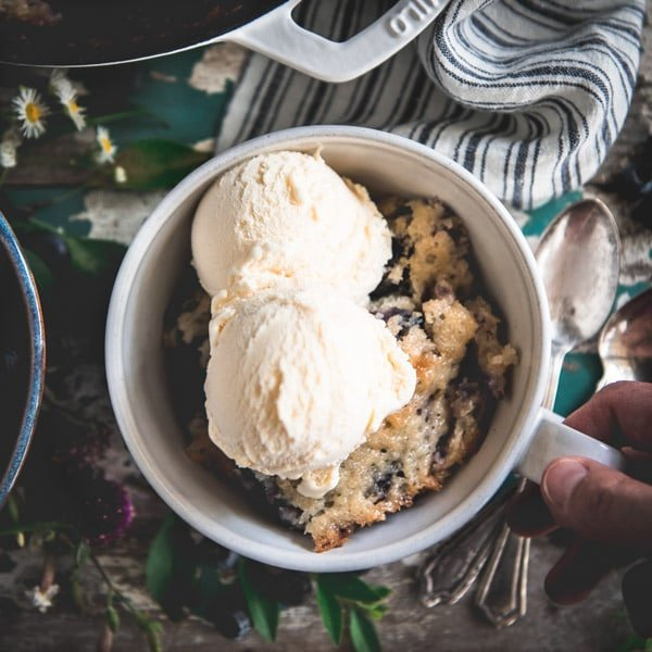 Hand holding a dish of old fashioned blueberry cobbler with vanilla ice cream