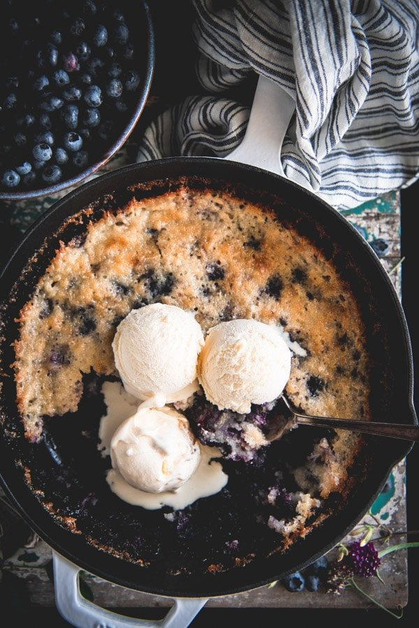 Close up shot of a skillet blueberry cobbler with three scoops of vanilla ice cream on top