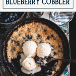Overhead image of the best blueberry cobbler recipe in a cast iron skillet with a text title box at top