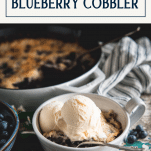 Bowl of old fashioned blueberry cobbler with vanilla ice cream and text title box on top
