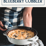 Hands holding an easy blueberry cobbler recipe with text title box at top
